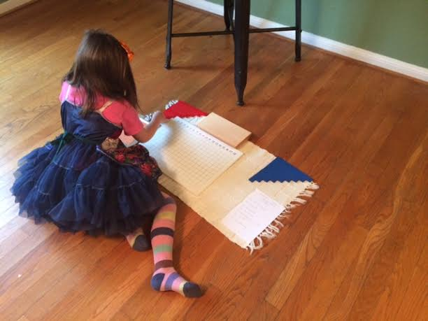 My daughter, in her interesting free choice outfit, doing the one piece of Montessori work we actually have! It is an addition board.